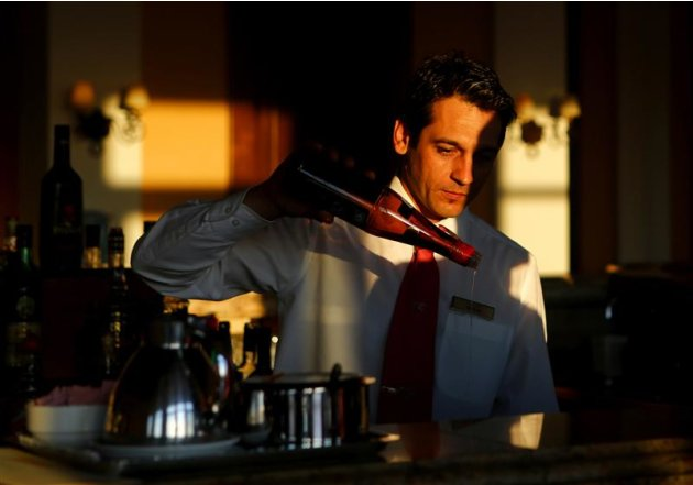 Vassilis Vassilakis prepares drinks at the bar of the Olympia Oasis Hotel at the Olympia Riviera resort in the town of Killini