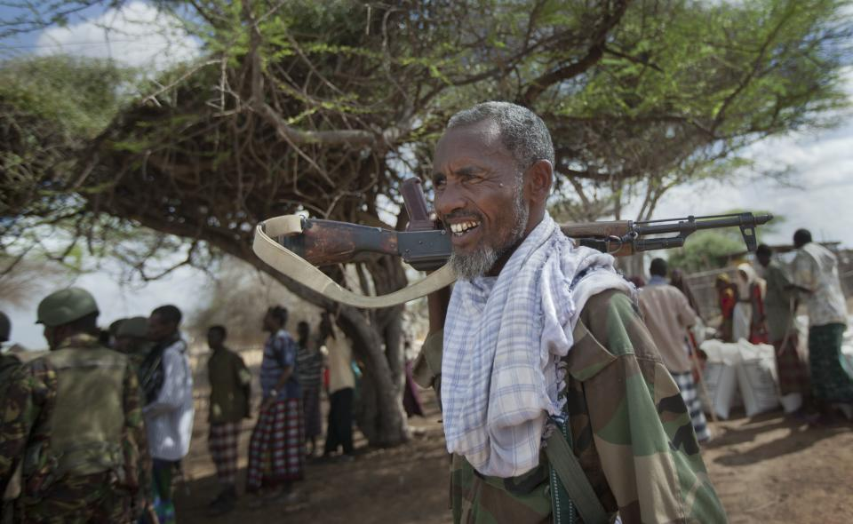 A Somali government soldier carries his weapon as Kenyan army soldiers speak to villagers in Tabda, inside Somalia Monday, Feb. 20, 2012. Kenya's military has been fighting inside Somalia in an ongoing offensive against militant group al-Shabab since October, when Somali gunmen carried out several kidnappings in Kenya. (AP Photo/Ben Curtis)
