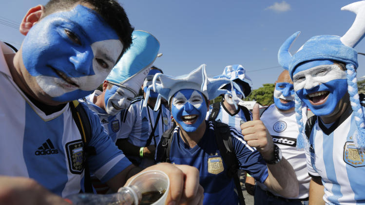 Argentinian fans cheer for the camera as they arrive to attend the group F World Cup soccer match between Argentina and Iran at the Mineirao Stadium in Belo Horizonte, Brazil, Saturday, June 21, 2014. (AP Photo/Sergei Grits)