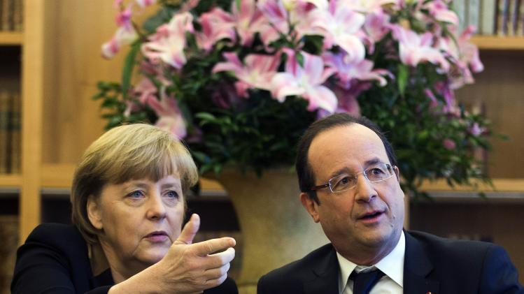 German Chancellor Angela Merkel, left, and French President Francois Hollande meet at the French embassy in Berlin during a day of celebrations marking the 50th Anniversary of the Elysee Treaty, Jan. 22, 2013. (AP Photo/Thomas Peter, Pool)