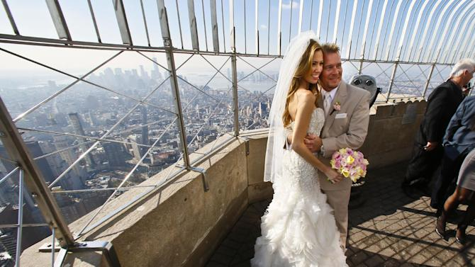 """Newlyweds Danielle Brabham, 39, and Michael Lynch, 41, from Miami Shores, Fla., pose for pictures at the Empire State Building viewing platform after their Valentine's Day wedding on Thursday, Feb. 14, 2013 in New York.   Brabham and Lynch were among three couples chosen for the 19th Annual Weddings Event, """"Love is in the Air,"""" designed by celebrity designer Preston Bailey, after submitting their personal love stories to the  Empire State Building's Facebook page.  (AP Photo/Bebeto Matthews)"""