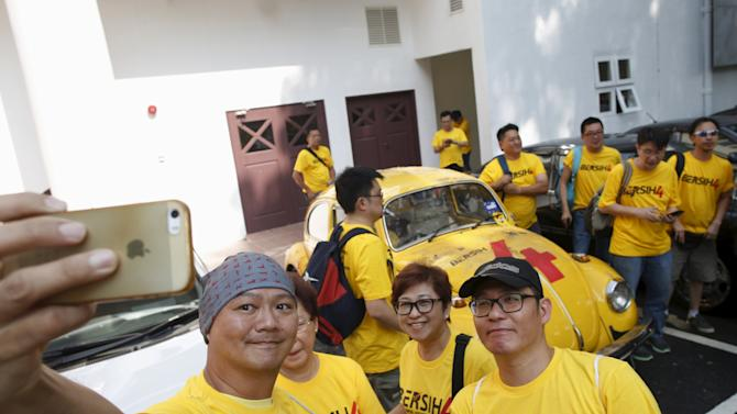 """Supporters of pro-democracy group """"Bersih"""" take selfie photos with a recently vandalised Volkswagen Beetle used to promote the rally, at the Kuala Lumpur and Selangor Chinese Assembly Hall, ahead of their march in Kuala Lumpur"""