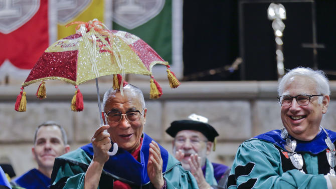 """The Dalai Lama holds a Mardi Gras umbrella, inscribed with the words """"Peace"""" and """"World Understanding"""" next to Tulane University President Scott Cowen, as local musicians perform at the university's 179th commencement ceremony at the Mercedes-Benz Superdome in New Orleans on Saturday, May 18, 2013. The Dalai Lama gave the commencement address. (AP Photo/Gerald Herbert)"""