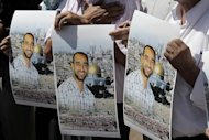 Protesters in Jerusalem hold portraits of Samer Issawi, a Palestinian prisoner on hunger strike, on September 18, 2012. The deteriorating health of prisoners on hunger strike in Israeli jails has sparked several mass protests across the Palestinian territories, some of which resulted in clashes with the army