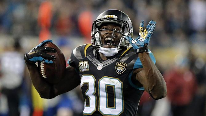 Jacksonville Jaguars running back Jordan Todman (30) smiles as he runs 62 yards for a touchdown against the Tennessee Titans during the fourth quarter of an NFL football game Thursday, Dec. 18, 2014, in Jacksonville, Fla. (AP Photo/Stephen B. Morton)