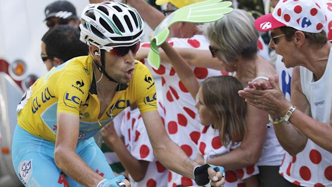 Italy's Vincenzo Nibali , wearing the overall leader's yellow jersey, breaks away in the final clim to win the thirteenth stage of the Tour de France cycling race over 197.5 kilometers (122.7 miles) with start in Saint-Etienne and finish in Chamrousse, France, Friday, July 18, 2014. (AP Photo/Christophe Ena)