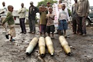 Congolese citizens look at tank shells lying next to the roadside, left behind by retreating government troops as they fled an assault by M23 rebels, in eastern Congo, Wednesday, Nov. 21, 2012. Thousands of Congolese soldiers and policemen defected to the M23 rebels Wednesday, as rebel leaders vowed to take control of all Congo, including the capital Kinshasa. The rebels organized a rally at Goma&#39;s Stadium of Volcanoes Wednesday after seizing control of the strategic city in eastern Congo Tuesday.(AP Photo/Marc Hofer)