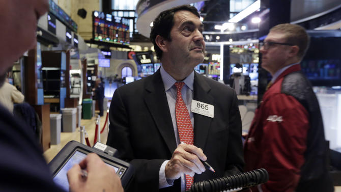 Trader Mark Muller, center, works on the floor of the New York Stock Exchange Tuesday, Jan. 27, 2015. U.S. stocks are tumbling in midday trading, weighed down by disappointing forecasts from big-name companies and an unexpected drop in orders of long-lasting goods. (AP Photo/Richard Drew)