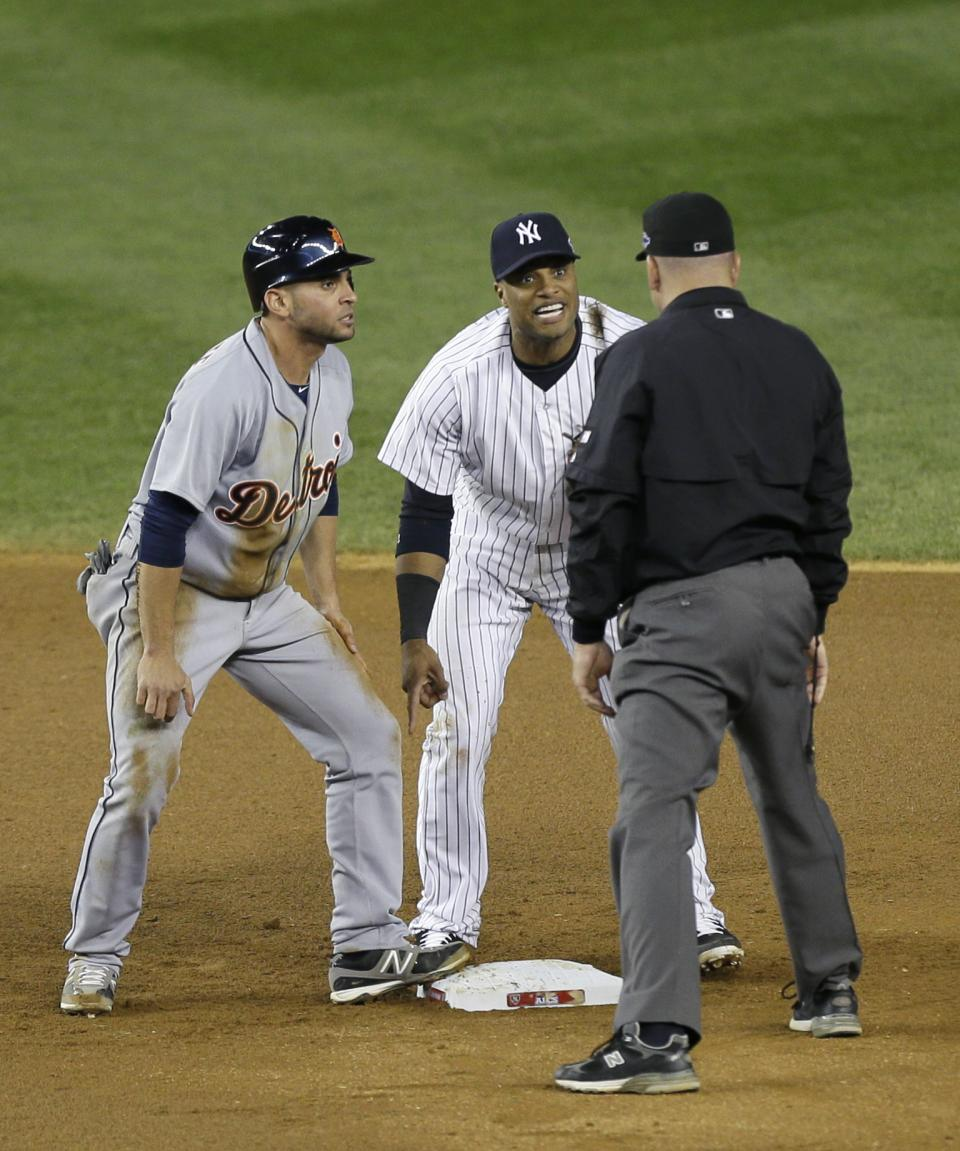 New York Yankees' Robinson Cano, center, complains to umpire Jeff Nelson after Nelson called Detroit Tigers' Omar Infante, left, safe at second base in the eighth inning of Game 2 of the American League championship series Sunday, Oct. 14, 2012, in New York. (AP Photo/Kathy Willens)