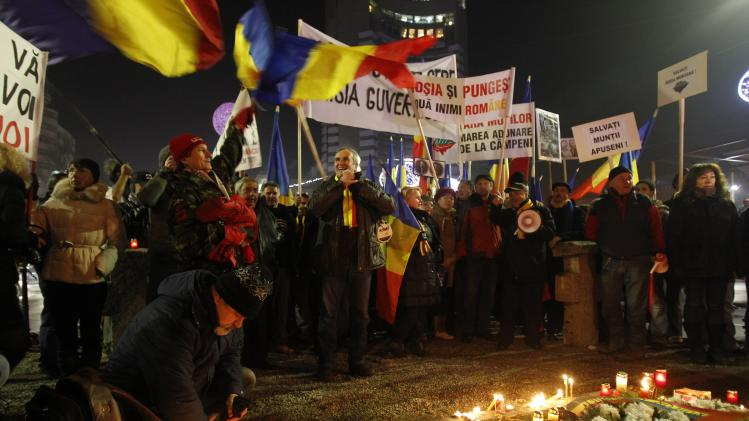 People shout slogans and wave the Romanian national flag during a protest in Bucharest