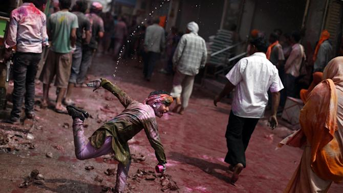 An Indian boy throws colored water on passers-by during holi celebrations outside Banke Bihari temple in Vrindavan, India, Wednesday, March 27, 2013. Holi, the Hindu festival of colors that also marks the advent of spring, is being celebrated across the country Wednesday. (AP Photo/Altaf Qadri)
