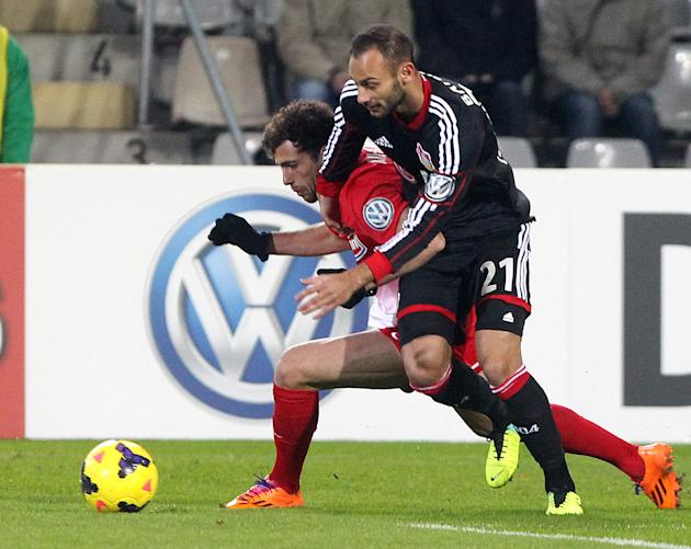 Freiburg's Admir Mehmedi of Switzerland, left, and Leverkusen's Omer Toprak of Turkey challenge for the ball during a round of 16 German soccer cup match between SC Freiburg and Bayer Leverkus