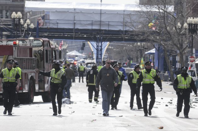 Public safety officials evacuate the scene after several explosions near the finish line of the 117th Boston Marathon in Boston