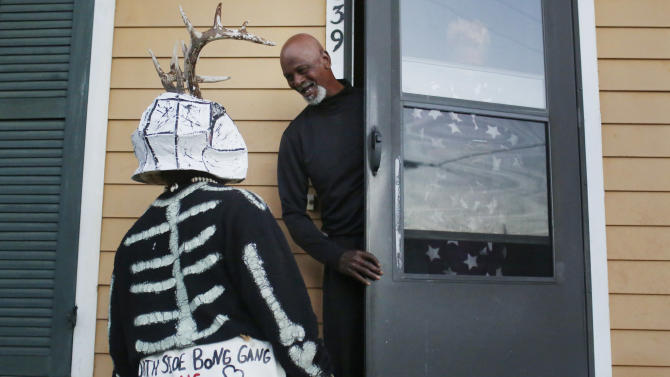 A member of the North Side Skull & Bone Gang, talks to a resident during the wake up call for Mardi Gras, Tuesday, Feb. 9, 2016, in New Orleans. (AP Photo/Brynn Anderson)