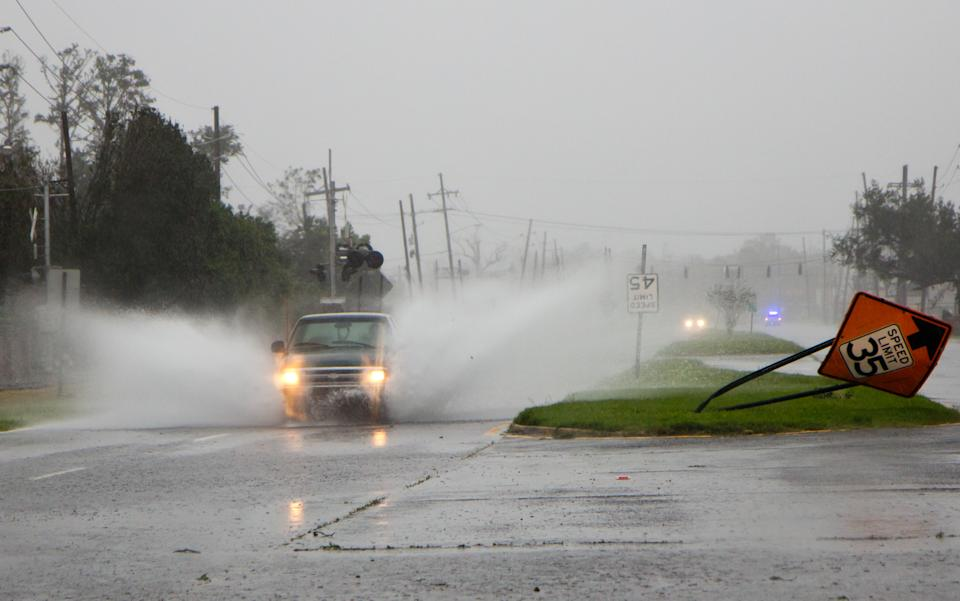 A pickup truck drives through standing water near Belle Chasse, La., in Plaquemines Parish, a rural area outside New Orleans that was flooded during Hurricane Isaac on Wednesday, Aug. 29, 2012. (AP Photo/Erik Schelzig)