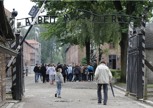 FILE- Tourists visit the former Nazi death camp of Auschwitz in Oswiecim, Poland, in this file photo dated Wednesday, June 6, 2012.  The Auschwitz-Birkenau memorial site in southern Poland registered 