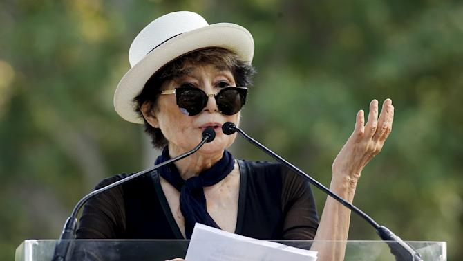 Artist Yoko Ono, widow of John Lennon, speaks to the guests before the unveiling of a tapestry honoring John Lennon at Ellis Island in New York