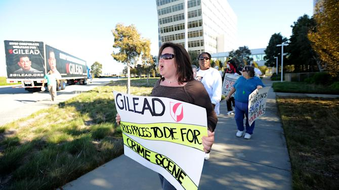 "Diane Sticker joins about 40 protesters from across the country converged on Gilead Sciences headquarters in Foster City, Calif., on Wednesday, Nov. 14, 2012, calling on the drug maker to lower prices for its Stribild AIDS medication. Joined by an 18-wheel tractor trailer adorned with a ""Stop Corporate Welfare for Gilead"" sign, picketers marched through streets around the company's headquarters for about an hour. (Noah Berger /AP Images for AIDS Healthcare Foundation)"