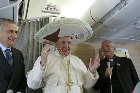 Pope Francis wears a Sombrero hat he received as a gift by a Mexican journalist aboard an airplane to Havana