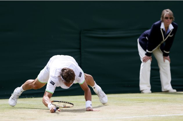 David Ferrer of Spain slips during his men's singles tennis match against Ivan Dodig of Croatia at the Wimbledon Tennis Championships, in London