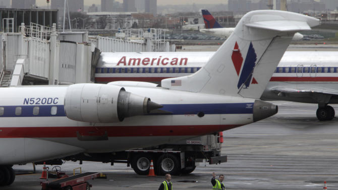 American Airlines' planes are parked at a gate at LaGuardia Airport in New York, Tuesday, Nov. 29, 2011. American Airlines and its parent company are filing for Chapter 11 bankruptcy protection as they seek to cut costs and unload massive debt built up by years of high jet fuel prices and labor struggles. (AP Photo/Seth Wenig)