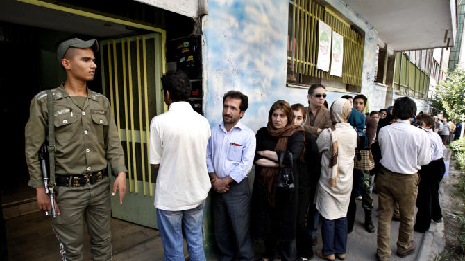 In this Friday, June 12, 2009 photo, an Iranian police officer stands guard as people line up outside a polling station in Tehran, Iran. Elections to pick Iran's next president are still five months away, but that's not too early for some warning shots by the country's leadership. The message to anyone questioning the openness of the June vote: Keep quiet. (AP Photo/Vahid Salemi)