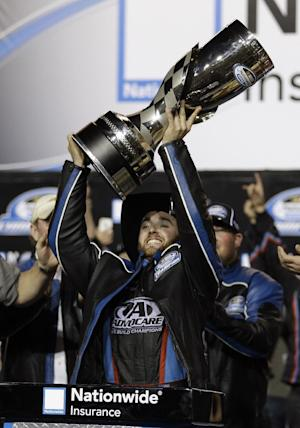 Austin Dillon hoists the trophy after he won the NASCAR Nationwide Series season title, Saturday, Nov. 16, 2013, at Homestead-Miami Speedway in Homestead, Fla. (AP Photo/Alan Diaz)