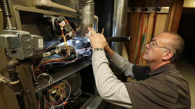 Frank Rojas, an employee of Bolls Heating and Cooling, clean and checks a gas furnace Tuesday, Nov. 13, 2012, in Indianapolis. An Indianapolis explosion that killed two people and decimated a neighborhood shows some signs that aren't typical of a natural gas explosion cause by an appliance but still could have been tied to a faulty furnace if conditions were right, experts said Tuesday. (AP Photo/Darron Cummings)