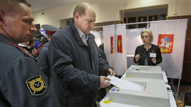 A man casts his ballot paper at a polling station in the town of Khimki outside Moscow, Russia, Sunday, Oct. 14, 2012. Russians are casting ballots in local elections that offer a degree of political competition but still remain tightly controlled by President Vladimir Putin's government. One of the most visible races Sunday is that for mayor of the town of Khimki, just outside Moscow. (AP Photo/Mikhail Metzel)