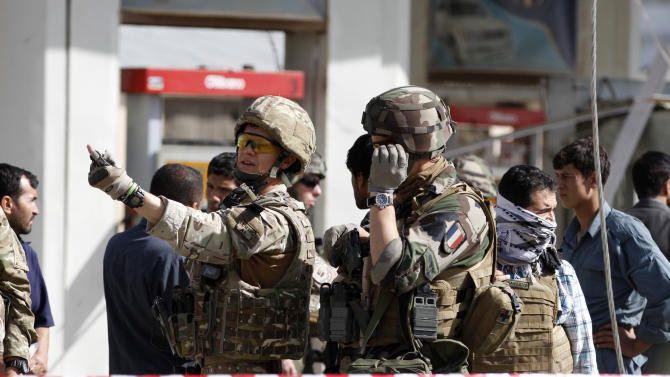 French soldiers arrive at the scene of a suicide bombing, Tuesday, Sept. 18, 2012 in Kabul, Afghanistan. A suicide bomber rammed a car packed with explosives into a mini-bus carrying foreign aviation workers to the airport in the Afghan capital early Tuesday, killing at least nine people in an attack a militant group said was revenge for an anti-Islam film that ridicules the Prophet Muhammad.  (AP Photo/Ahmad Jamshid)