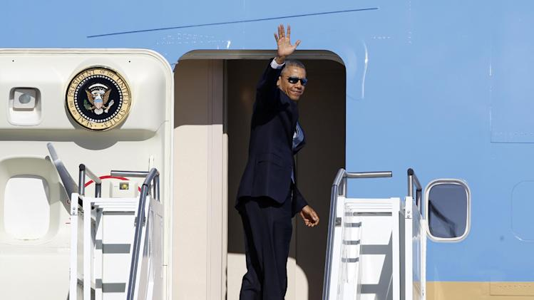 President Barack Obama waves in the direction of members of the media as he boards Air Force One at Palm Springs International Airport, Saturday, June 14, 2014, in Palm Springs, Calif. Obama is traveling to Orange County to deliver the commencement address for graduates at the University of California, Irvine at Angel Stadium in Anaheim, Calif. (AP Photo/Alex Gallardo)