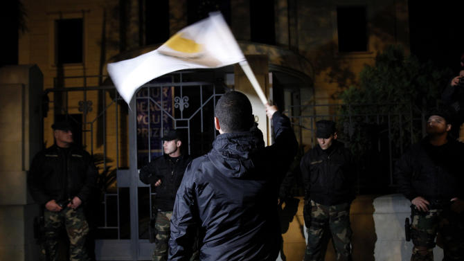 A protestor waves a Cyprus flag in front of riot policemen during an anti-bailout rally outside of European Union house in Nicosia, Cyprus, Sunday, March 24, 2013. After failing for a week to find a solution to a crisis that could force their country into bankruptcy, Cypriot politicians turned to the European Union on Sunday in a last-ditch effort to help the island nation forge a viable plan to secure an international bailout. (AP Photo/Petros Karadjias)