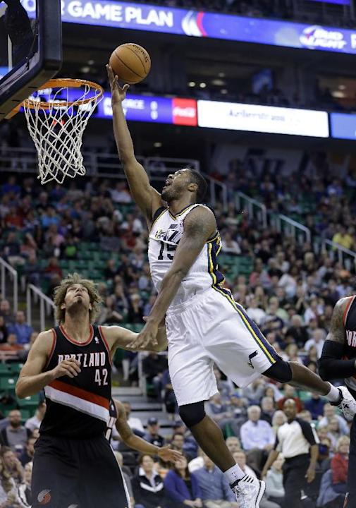 Utah Jazz's Derrick Favors (15) lays the ball up as Portland Trail Blazers' Robin Lopez (42) looks on in the second half during an NBA preseason basketball game Wednesday, Oct. 16, 2013, in Salt Lake