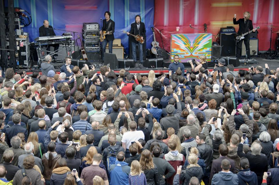 Crowds gather to watch Sir Paul McCartney, centre, and his band in Covent Garden, London, Friday, Oct. 18, 2013. The surprise gig lasted for 20 minutes during lunchtime following a similar appearance in New York last Friday. (Photo by Jonathan Short/Invision/AP)
