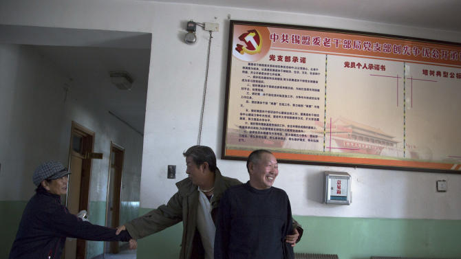 In this photo taken on Wednesday, Oct. 24, 2012, retired employees of a government office have a light moment at an old hospital administration building in Xilinhot in northern China's Inner Mongolia. Buying and selling office is so rampant in China that it has eroded public trust in officialdom, undermining the ruling Communist Party's image as an institute that promotes the competent, not the connected. Even though Chinese leaders have vowed to eradicate the practice, it has showed no sign of abatement. (AP Photo/Andy Wong)