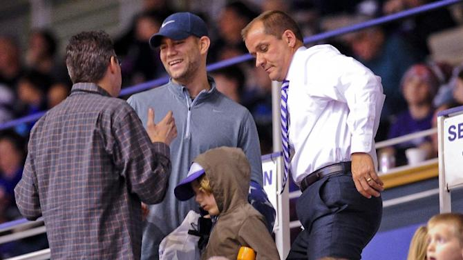 Theo Epstein, center, president of baseball operations for the Chicago Cubs and James Phillips, right, athletic director of Northwestern, talk with fans during the second half of an NCAA college basketball game Monday, Dec. 22, 2014, in Evanston, Ill. (AP Photo/Matt Marton)
