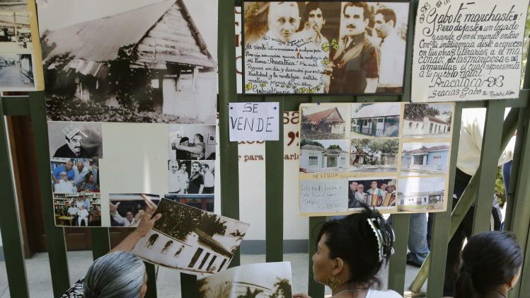 Residents look at pictures in front of a museum converted from the house Colombian author Gabriel Garcia Marquez grew up in, at Aracataca