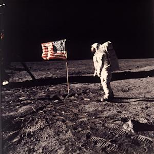"""FILE - In this July 20, 1969 file photo provided by NASA shows astronaut Edwin E. """"Buzz"""" Aldrin Jr. posing for a photograph beside the U.S. flag deployed on the moon during the Apollo 11 mission. Aldrin and fellow astronaut Neil Armstrong were the first men to walk on the lunar surface. The trio was launched to the moon by a Saturn V launch vehicle at 9:32 a.m. EDT, July 16, 1969. They departed the moon July 21, 1969. (AP Photo/NASA, Neil Armstrong, File)"""