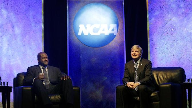 NCAA President Mark Emmert, right, speaks as former NBA great Shaquille O'Neal watches at the NCAA's convention keynote luncheon Wednesday, Jan. 16, 2013, in Grapevine, Texas. O'Neal spoke about the importance of education in his life and the value his three degrees bring in his post-NBA basketball career. (AP Photo/LM Otero)