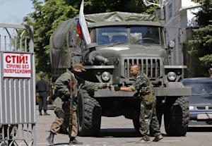 Pro-Russian fighters stand next to a truck with a Russian…