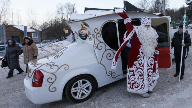 A man dressed as Father Frost, Russian equivalent of Santa Claus, welcomes people as he leaves a car during a children's celebration at Father Frost's forest residence set up inside a local zoo in the Taiga district, outside Krasnoyarsk