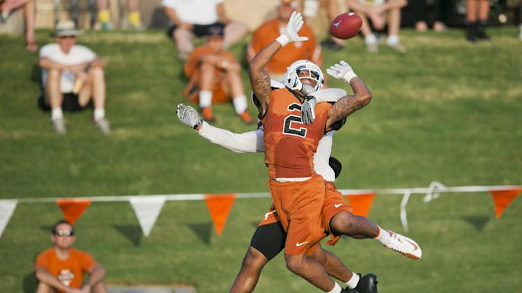 Texas wide receiver Kendall Sanders (2) tries to make a play on the ball against safety Adrian Phillips in front of fans during the first day of the team's NCAA college football open practice on the campus of University of Texas at Austin on Thursday, Aug. 8, 2013, in Austin, Texas. (AP Photo/Austin American-Statesman, Ricardo B. Brazziell)