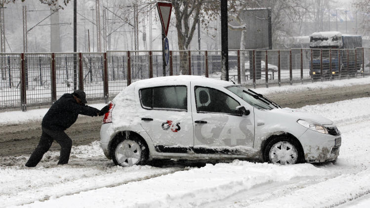 A man pushes a car on a snow covered street in Belgrade, Serbia, Sunday, Dec. 9, 2012. Freezing temperatures and heavy snowfall have killed at least 5 people and caused travel chaos across the Balkans. (AP Photo/Darko Vojinovic)