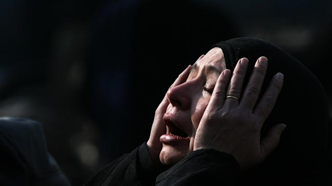 FILE - In this Dec. 6, 2006 file photo an Iraqi woman grieves over the death of her relative who was killed in violence in Baghdad, Iraq. As the country enters a post-U.S. era, many Iraqis who had welcomed the 2003 invasion and hoped for better lives feel they remain in even more danger than before Saddam's fall. (AP Photo/Hadi Mizban, File)