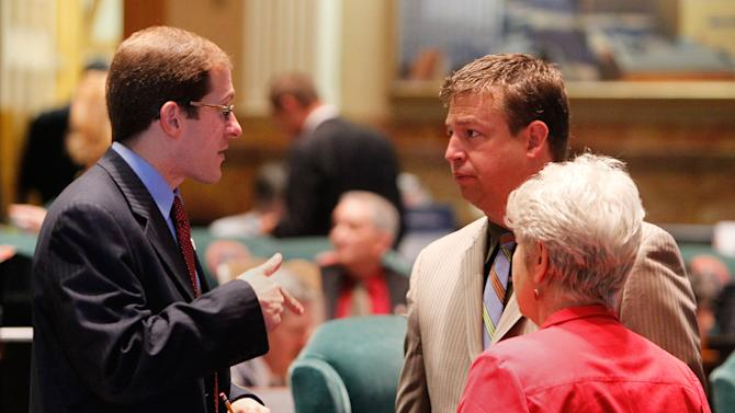House Minority Leader Mark Ferrandino, left, D-Denver, talks with House Speaker Frank McNulty, center, R-Highlands Ranch, and Rep. Lois Court, D-Denver, at the Capitol in Denver on Wednesday, May 9, 2012. Wednesday was the last day of the session. (AP Photo/Ed Andrieski)