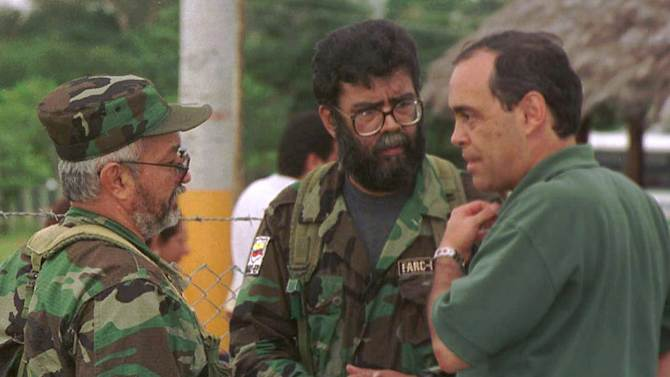 FILE - In this May 21, 2000 file photo, Colombia's Peace Commissioner Camilo Gomez, right, talks to Revolutionary Armed Forces of Colombia (FARC) leaders Alfonso Cano, center, and Raul Reyes, during peace talks in Los Pozos, in southern Colombia.  According to Colombian military authorities, Cano, the top FARC commander, was killed in a military operation on Friday Nov. 4, 2011.  (AP Photo/Fernando Ruiz, File)