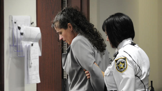 """Dee Dee Moore is led from a Hillsborough County courtroom after being found guilty of first-degree murder in the death of lottery winner Abraham Shakespeare Monday, Dec. 10, 2012 in Tampa, Fla. Moore was convicted Monday of first-degree murder in the slaying of a lottery winner in central Florida and sentenced to mandatory life without parole by a judge who called her """"cold, calculating and cruel.""""(AP Photo/The Tampa Tribune, Chris Urso, Pool)"""