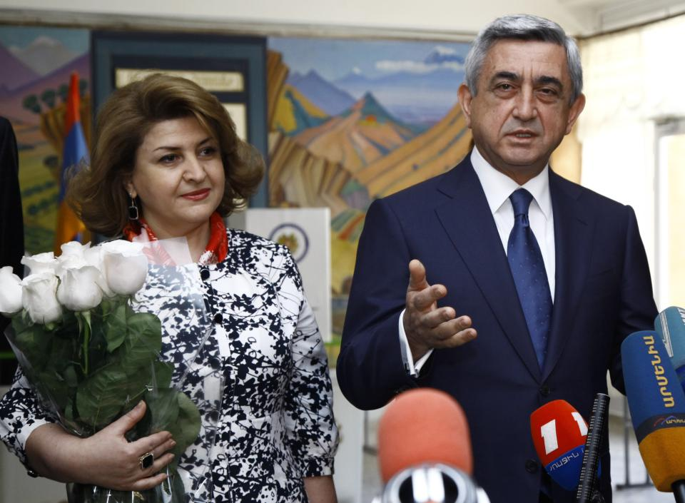 Armenian President and Republican Party President Serge Sarkisian speaks to press after he voted during parliamentary elections in Yerevan, Armenia on Sunday, May 6, 2012 President's wife Rita Sarkisian smiles at  left. (AP Photo/PanARMENIAN , Tigran Mehrabyan)