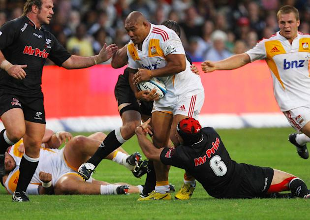 New Zealand Waikato Chiefs' Arizona Taumalolo (C) is tackled by Durban Sharks' players during a Super 15 rugby union match at the Mr Price Kings Park Rugby Stadium on April 21, 2012.  AFP PHOTO (Photo