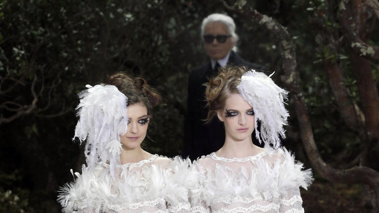 FILE - This Jan. 22, 2013 file photo shows two models wear wedding gowns by German fashion designer Karl Lagerfeld for Chanel's Spring Summer 2013 Haute Couture fashion collection, in Paris. Lagerfeld used fashion to support a controversial French gay marriage law, sending two brides together down the catwalk. (AP Photo/Christophe Ena, File)